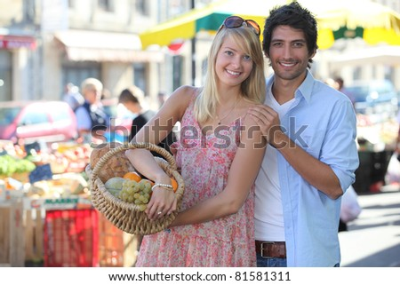 Couple at a market with basket of produce - stock photo