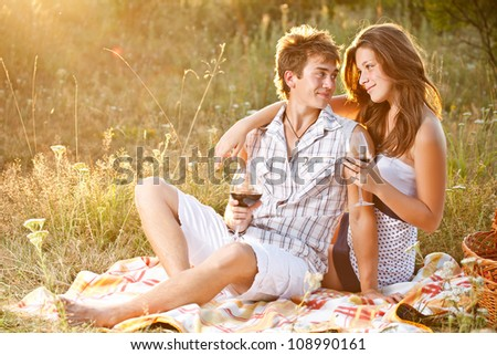 Couple at a picnic in meadow - stock photo