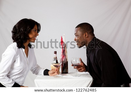 Couple at a quiet, romantic table with wine and candle, talking and getting to know each other - stock photo