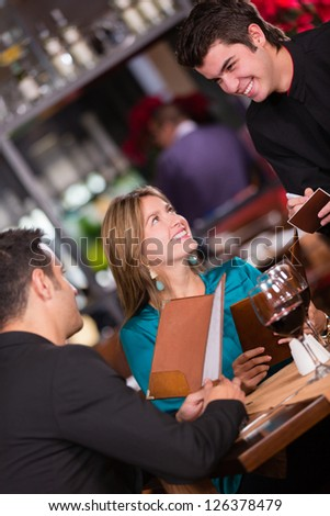 Couple at a restaurant ordering to the waiter - stock photo