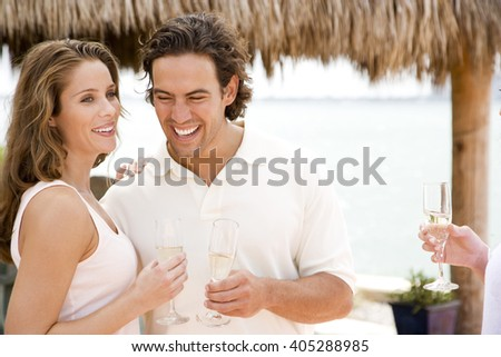 Couple at a tropical hotel bar, having a drink - stock photo