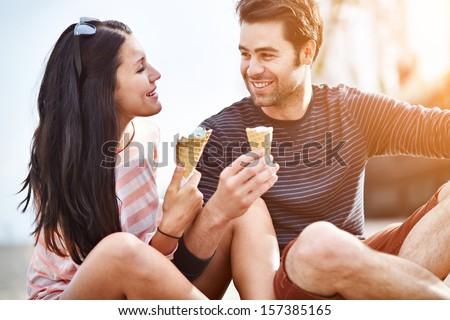 couple at amusement park sharing ice cream - stock photo