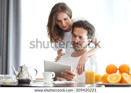 couple at breakfast looking at tablet - stock photo