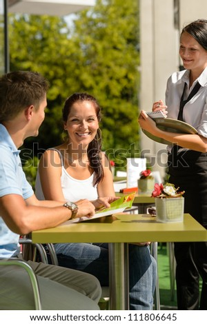 Couple at cafe ordering from menu waitress man point menu - stock photo