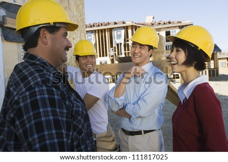 Couple at construction site talking to workers - stock photo
