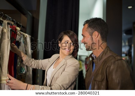 Couple at fashion store buying clothes and smiling