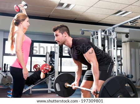 Couple at gym weightlifting workout barbell and dumbbell fitness - stock photo