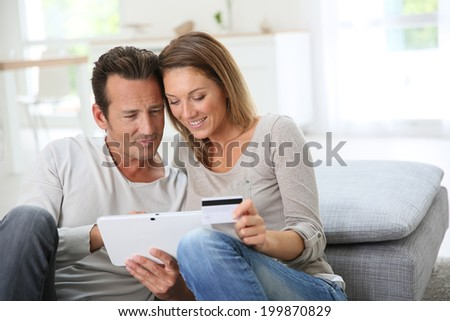 Couple at home buying on internet - stock photo