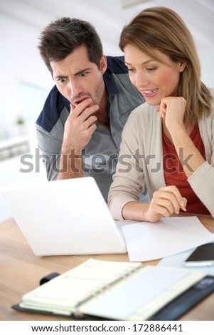 Couple at home checking accounts on internet