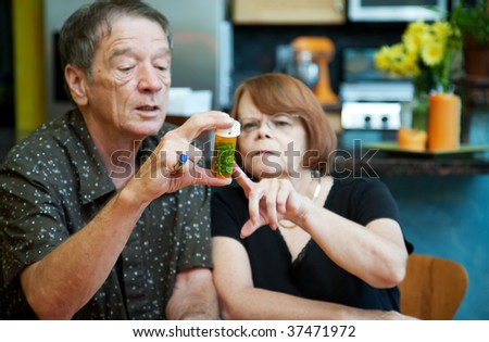 Couple at Home Considering Medication in Bottle - stock photo