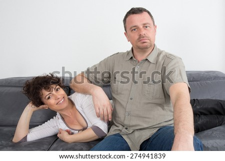Couple at home lying on their sofa relaxing