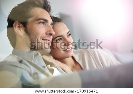 Couple at home relaxing in sofa - stock photo