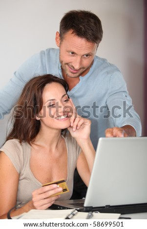 Couple at home shopping on internet - stock photo