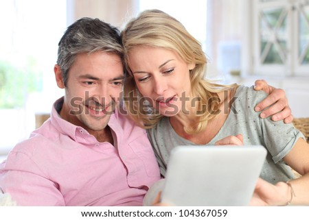 Couple at home using electronic tablet - stock photo