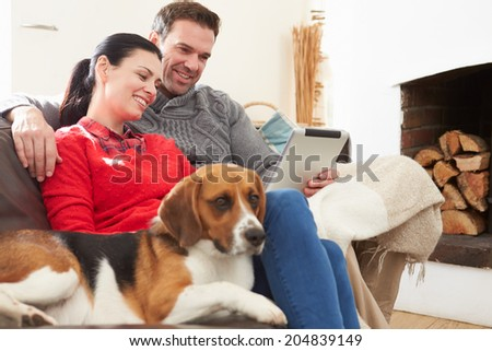Couple At Home With Pet Dog Looking At Digital Tablet