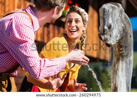 Couple at mountain hut drinking water from source well, scene set in the Alps with traditional clothing - stock photo