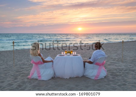 Couple at sea beach during luxury romantic dinner, with candles and torches flame against beautiful sunset - stock photo