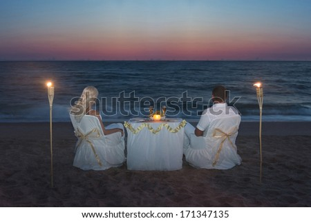 Couple at sea beach during luxury romantic dinner, with candles and torches flame against beautiful sunset