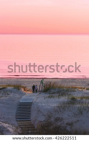 Couple at the beach at sunset in Ventspils, the Baltic Sea. Ventspils a city in the Courland region of Latvia. Latvia is one of the Baltic countries - stock photo