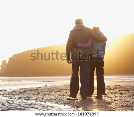 Couple at the beach holding hands - stock photo