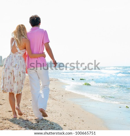 Couple at the beach holding hands and walking. Sunny day, bright colors. Europe, Spain, Costa Blanca. Photo from Behind - stock photo