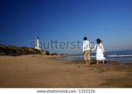 Couple at the beach holding hands walking towards the lighthouse - stock photo