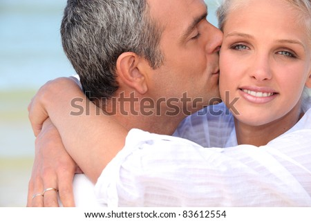 Couple at the beach kissing - stock photo