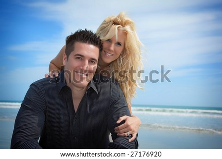 Couple at the beach looking into camera. - stock photo
