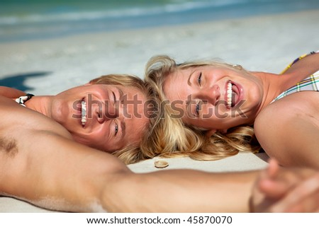 Couple at the beach lying on sand, laughing - stock photo
