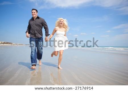 Couple at the beach running. - stock photo