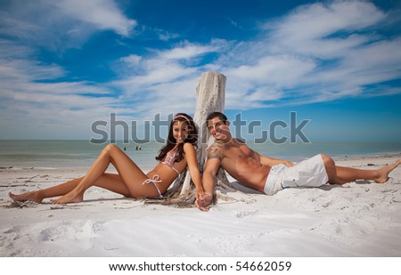 Couple at the beach, sitting - stock photo