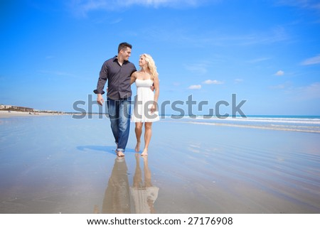 Couple at the beach walking and talking - stock photo