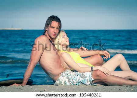 Couple at the beach with surfboard. - stock photo
