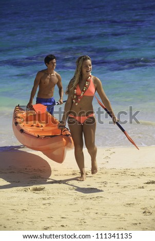 couple at the beach with their kayak - stock photo