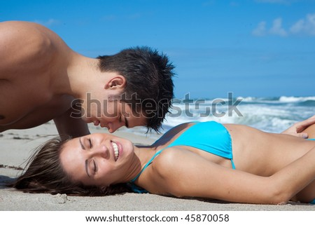 Couple at the beach,  woman smiling. - stock photo
