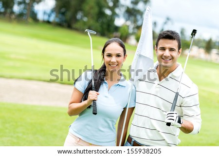 Couple at the course playing golf and looking happy  - stock photo