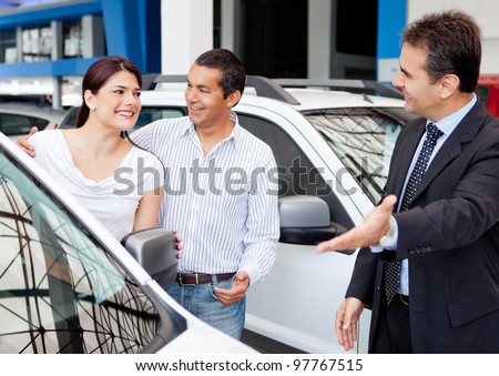 Couple at the dealership buying a new car - stock photo