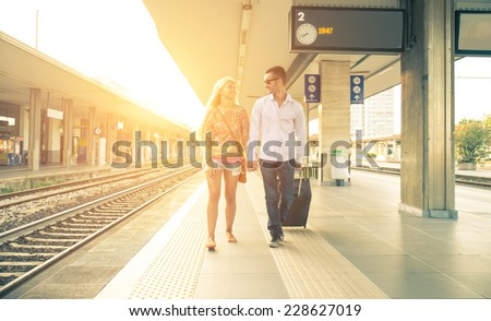 couple at the train station. man need to take a train and his girlfriend is saying goodbye - stock photo