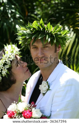 couple at Tropical wedding with flowers crowns - stock photo