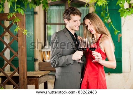 Couple at winetasting with red wine in a restaurant - stock photo