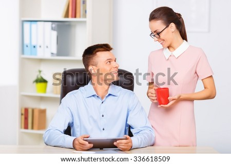 Couple at work.  Female coworker holding a cup of coffee for her office boyfriend.