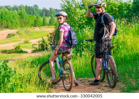 couple athletes on the mountain bike resting on a hill - stock photo