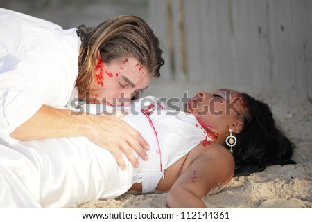 Couple attacked on the beach - stock photo