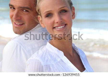 Couple back to back on the beach - stock photo