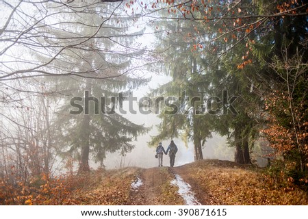 Couple backpackers hiking on the autumn/early winter path in mountains during their vacation trip. - stock photo