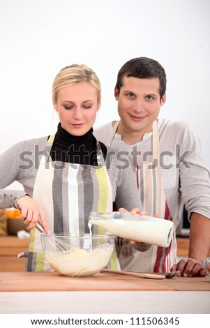 Couple baking together in kitchen - stock photo