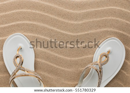 Couple beach white flip flops encrusted with rhinestones standing on the sand, with space for your text