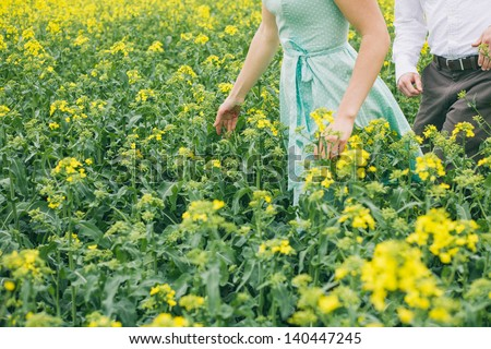 Couple before wedding running in colza field, girl with turquoise dress, without face, vintage color, engagement photo - stock photo