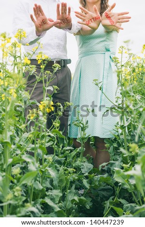 Couple before wedding with red sign on their hands, we are getting married, colza field, romantic photo, engagement photo, girl with turquoise dress, vintage color - stock photo