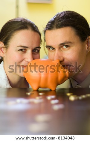 Couple behind piggy bank and some coins in front - stock photo